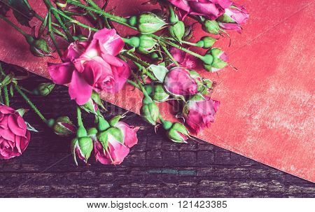 Bouquet Of Pink Roses On A Red Sheet Of Paper