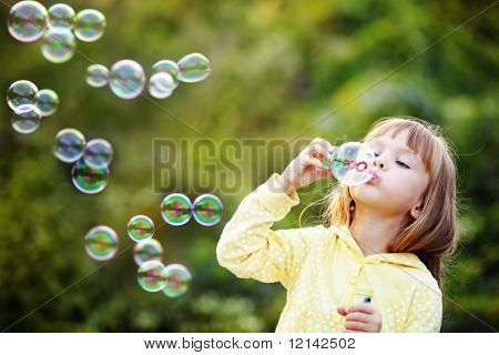 Portrait of funny lovely little girl blowing soap bubbles poster