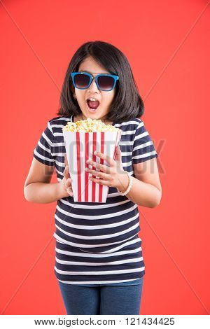 happy girl eating popcorn, indian girl eating popcorn, isolated on red