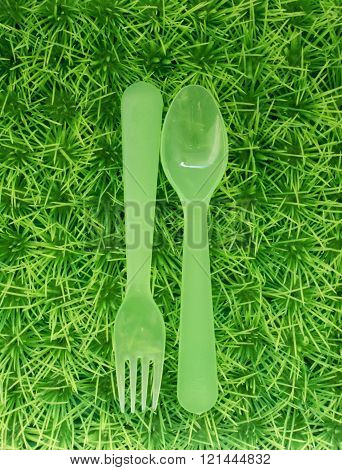 Green spoon and fork on a green lawn