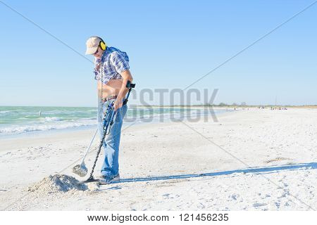 FORT DESOTO BEACH,USA:2016.3.6 The man on  the beach is working on metal detector to find some antique coins and jewelry for hobby and recreation