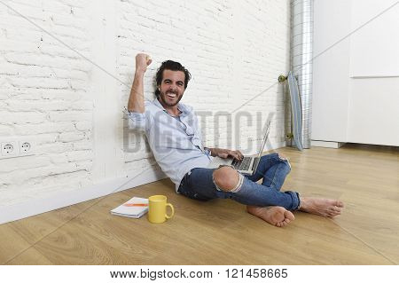 young attractive latin man in hipster and modern casual style look sitting happy on unfurnished living room home floor working on laptop computer gesturing excited on victory and success