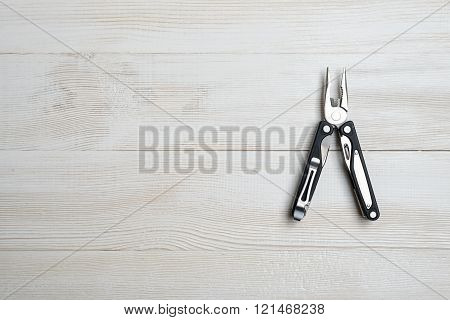 Multi tool with black handles on a white wooden background. Top view of desktop
