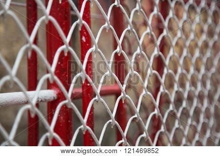 Close up of white and red metal chain fence