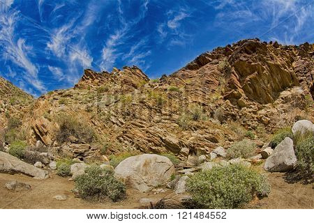 Scenic view of a rugged, rocky mountainside framed against a blue sky. Mo poster