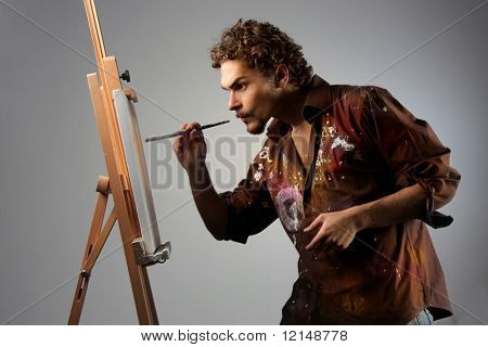 young man painting on a canvas
