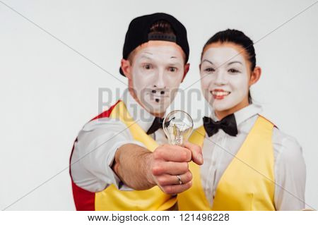 studio shot of two mimes isolated on a white background. with lamp and bulb
