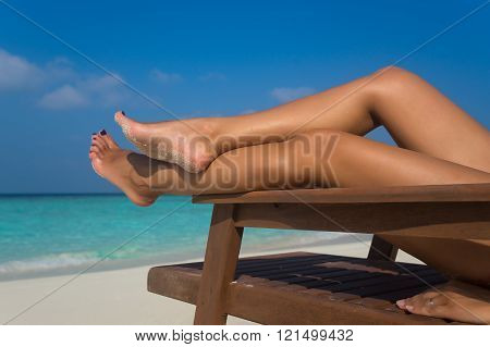 Young Woman Sunbathing On Lounger. Legs.