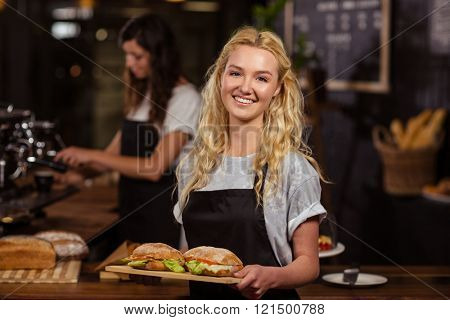 Pretty waitress holding a tray with sandwiches at the coffee shop