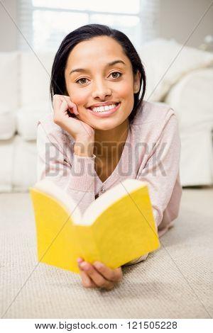 Smiling brunette reading book lying on carpet