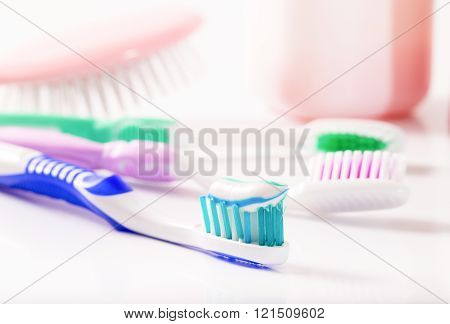 Toothbrushes and hairbrush in pastel tones. Group of white-pink objects on subject of hygiene. Close up small depth of sharpness