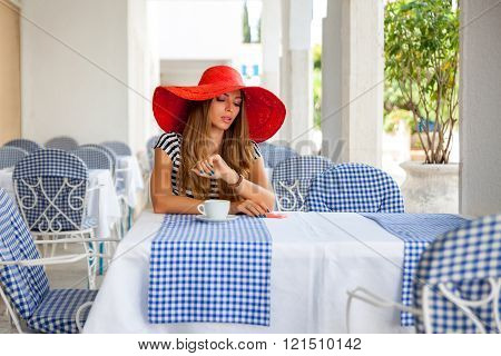 Beautiful woman sitting in a summer cafe