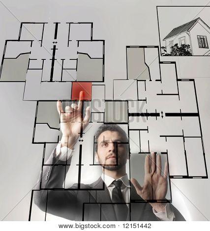 a businessman touching a digital blueprint of home