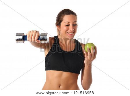 Happy young woman holding a dumbbell and a green apple
