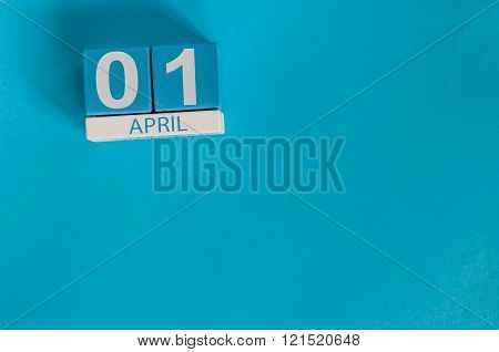 April 1st. Image of april 1 wooden color calendar on blue background.  Spring day, empty space for t