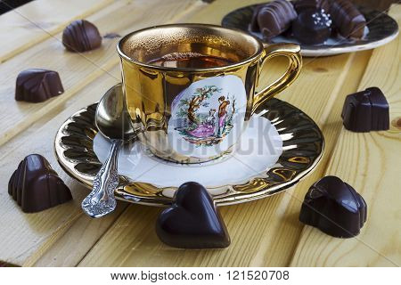 Close up of a cup of tea with chocolate candies on wood