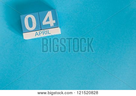April 4th. Image of april 4 wooden color calendar on blue background.  Spring day, empty space for t
