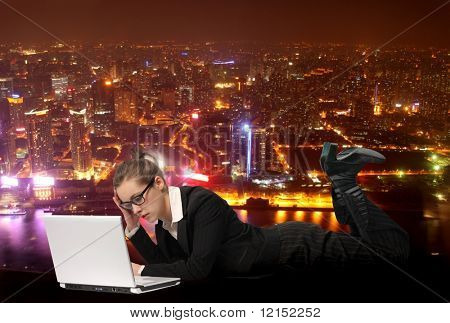 business woman using laptop with city on the background