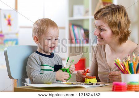 Woman teaches child handcraft