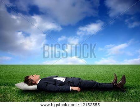 Business man sleeping on a grass field