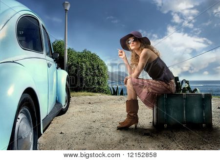 woman with baggage near to vintage car