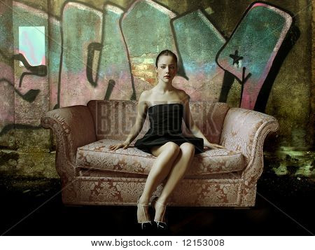 elegant woman sitting on a sofa against a painted wall