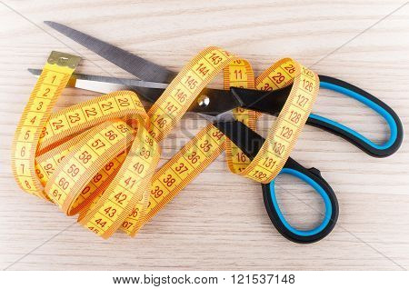 Sartorial Scissors And Tape-line On Wooden Table