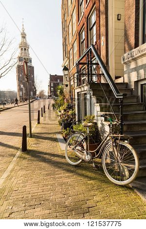 AMSTERDAM NETHERLANDS - 17TH FEBRUARY 2016: The outside of a building in Amsterdam in the morning. A bicycle can be seen parked up outside.