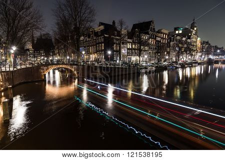 A view of the bridges at the Leidsegracht and Keizersgracht canals intersection in Amsterdam at dusk. Bikes and buildings can be seen. The trail from a boat can be seen. poster