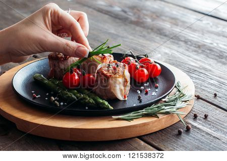 Food  decorating. Chef decorating a pork dish.