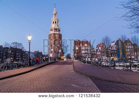 A view along Oudeschans Street towards the Montelbaanstoren Tower in Amsterdam at twilight. Building boats and bikes can be seen.