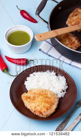 Schnitzel with rice and sauce on blue wooden table.