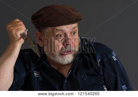 Malicious senior man holding rusty knife