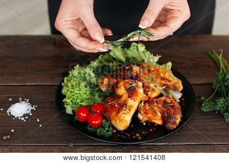 Chief decorated spicy chicken on wooden table