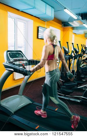 Athletic girl jogging on treadmil in gym
