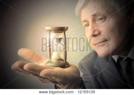 senior businessman looking at hourglass
