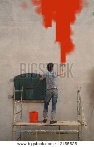 rear view of man painting in red colour an external wall