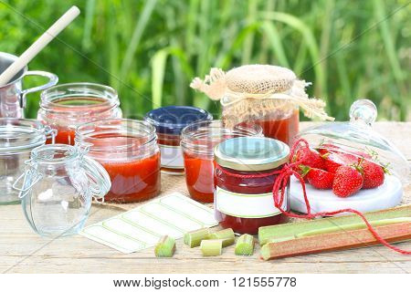 strawberries and rhubarb are processed into jam and bottled in glasses