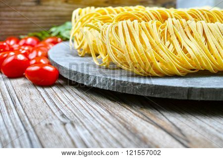 Homemade Fettuccini Pasta, Small Red Tomatoes On Wooden Plate