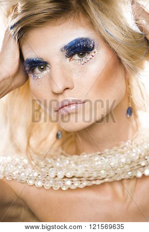 beauty young snow queen in fairy flashes with hair crown on her head close up in cold blue light