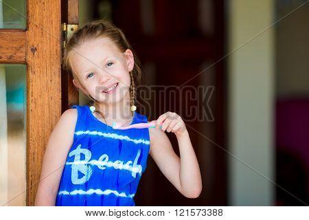 Little girl brushing her teeth in bathroom