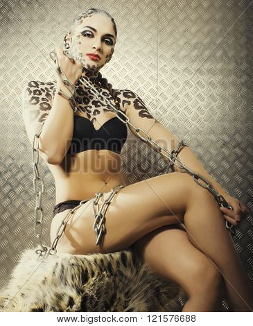 young sexy woman with leopard make up all over body, cat bodyart closeup sensual