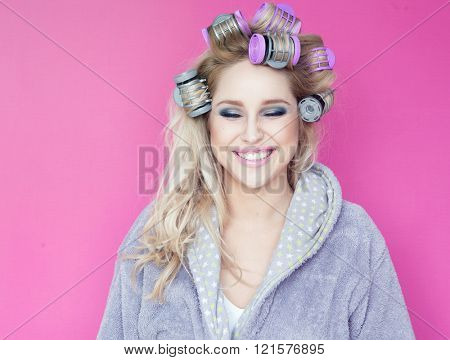 Young attractive happy blonde woman wearing a bathrobe with hot rollers beauty concept