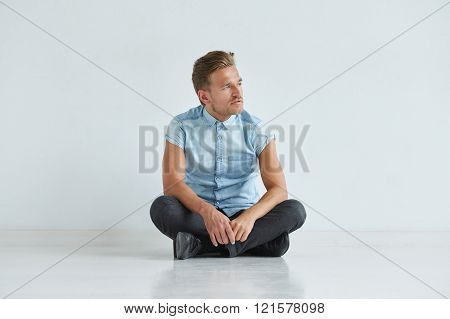 Brutal man in a shirt with short sleeves sitting in lotus posture white background and floor looking