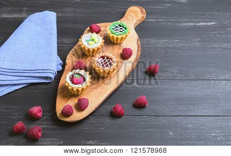 Small cakes petit fours in the form of baskets with cream and jam on a wooden plank from a tree of olive blue cloth worn on a dark black background in rustic style Empty place for text
