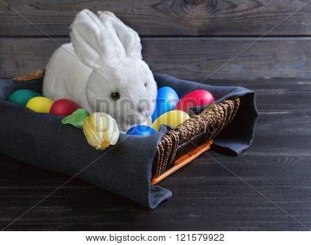 on the feast of Easter card in form of wicker basket with colorful dyed eggs Easter white rabbit tulip flower on a dark black wooden background in rustic style there is an empty space for your text