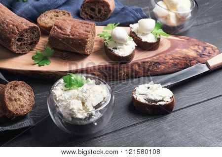 On a dark black wooden background small sandwiches canape bagget rye bread mozzarella Philadelphia cheese celery knife