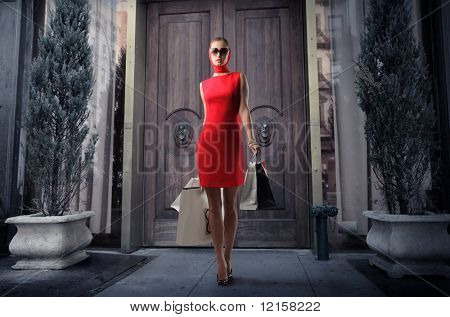 attractive girl in red dress with shopping bags outside a boutique