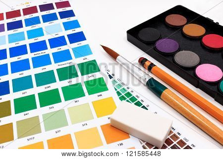 Brushes, watercolor classroom pack,eraser and abstract colored palette guide on table.