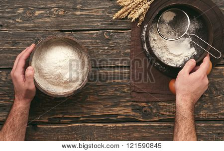 baker sifting the flour on dark wooden table, top view